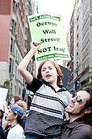 "Ty Hailey and son Gaige join the thousands of people marching up 6th Avenue to Times Square on October 15, 2011 in New York City in support of the ""Occupy Wall Street"" movement."