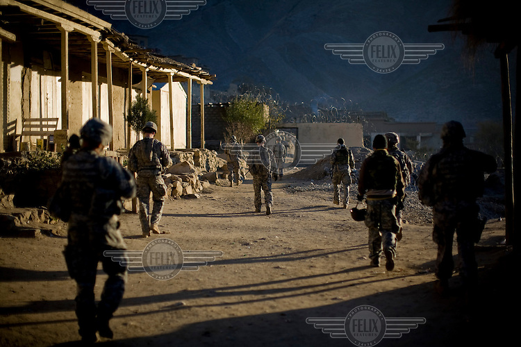 Soldiers from Charlie Company, 3rd Platoon patrol in Nanglam village in the Pesh Valley in Kunar. The unit was providing security for a local English school graduation ceremony in an effort to maintain support from the local community and stabilise the security in this pro-Taliban region.