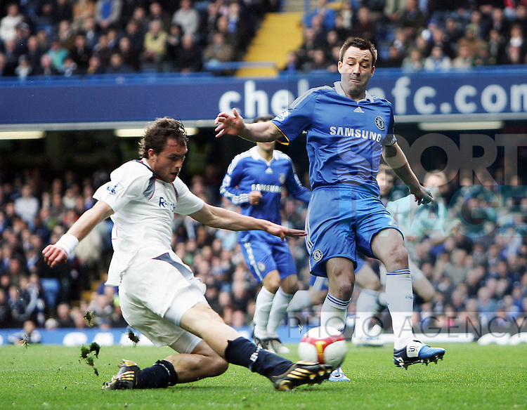 Johan Elmander of Bolton Wanderers shoots past John Terry of Chelsea