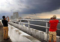 RICK WILSON/The Times-Union--6/26/09--San Marco residents Shawn Wallace (left) and Greg Morris snap souvenir pictures from atop the Acosta Bridge as a waterspout moves in the St. Johns River just south of the Interstate 95 Fuller Warren Bridge in downtown Jacksonville, Fl. Friday afternoon June 26, 2009.  (The Florida Times-Union, Rick Wilson)