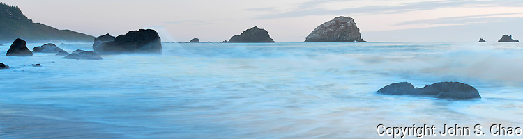 Panorama of incoming tide by False Klamath Cove sea stacks at dusk, Redwood National & State Parks, California.