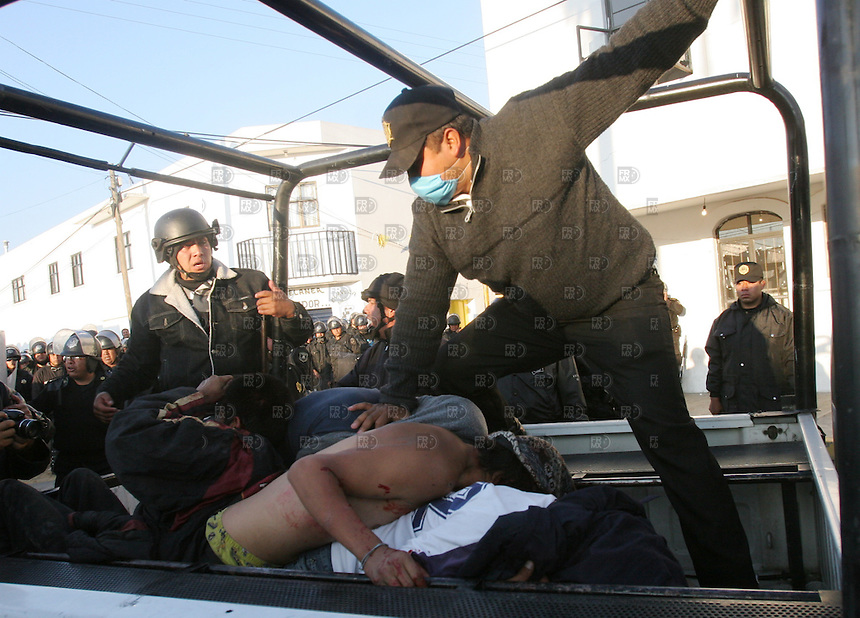 Policias municipales y de la PFP  sacan a  una persona en el pueblo de San Salvador Atenco  para desalojar a los miembros del Frente del Pueblo en Defensa de la Tierra,  el jueves 4 de mayo de 2006. Foto: Alejandro Meléndez