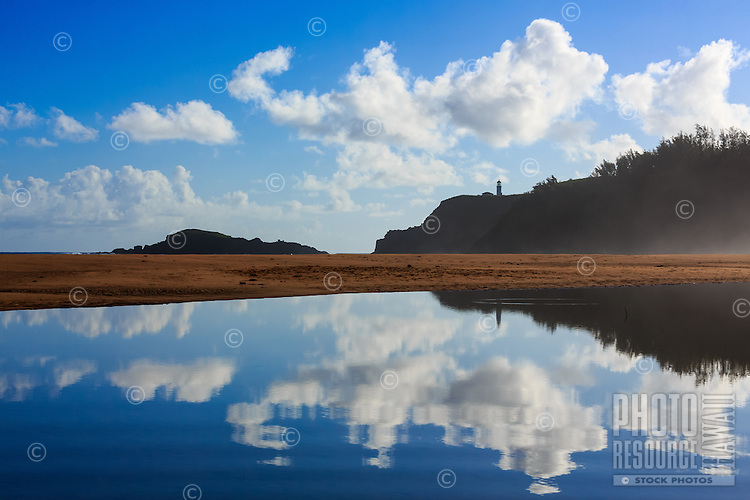A distant Kilauea Lighthouse with blue sky and clouds reflected in a rippling tidal pool at Secrets (or Secret) Beach, Kaua'i.