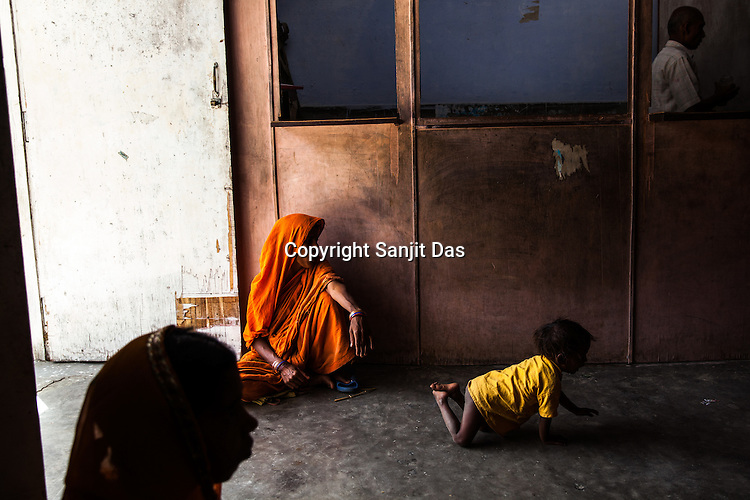 25 year old Dayawati plays with her 17 month son, Naresh Mukhiya while they wait to meet the Health post incharge at the local health centre in Hanuman Nagar in Saptari, Nepal. <br /> Naresh Mukhiya was first admitted on July 17, 2013 when he was 9 months old. MUAC - 109 mm, Weight - 5.5kg, and Height - 65 cm. He was discharged on Oct 1st, 2013. MUAC at the time of discharge - 123, Weight - 6.5 Kg, Height - 66cm. Total RUTF consumes - 148 sachets.Gain of weight - 2gm.day.