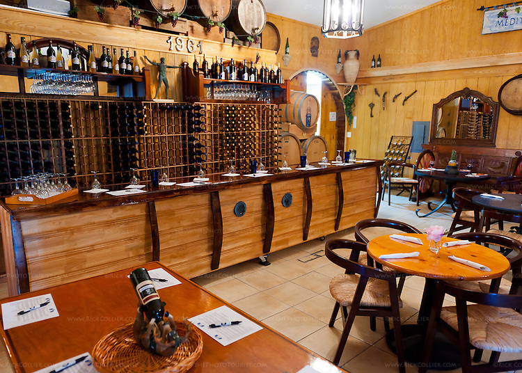 The barrel-themed overflow tasting room or event room at Mediterranean Cellars has a number of tables and an attractive barrel-themed bar.