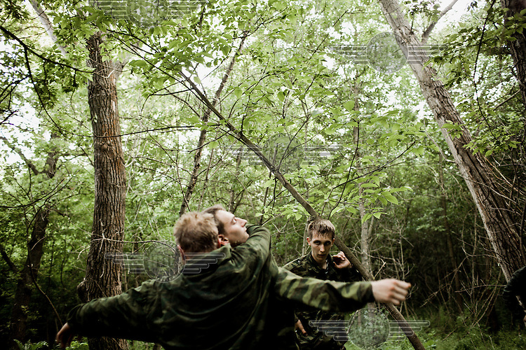 Youth members of a Cossack civil defence force practice martial arts in a forest in the Caucasus Mountains.