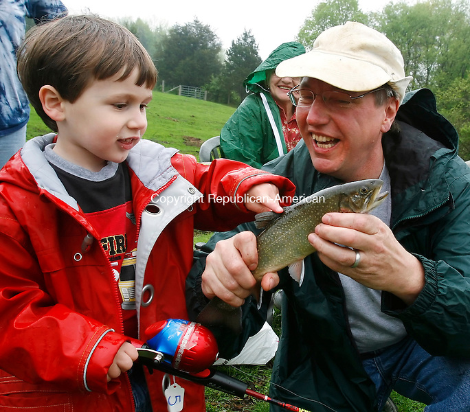 WOODBURY, CT, 05/09/09- 050909BZ02- Zack Hellwinkle, 4, of Woodbury, touches a Brook Trout held by his father Don Hellwinkle during the 5th annual mel Snyder Fishing Derby at King's Pond on Railtree Hill Road Saturday morning.  This was the tenth fish he caught including the first fish of the entire derby which earned him a small trophy.<br /> Jamison C. Bazinet Republican-American
