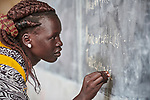 A woman writes on a blackboard in an English class in the Arrupe Learning Center, run by Jesuit Refugee Service in Bunj, South Sudan. Participants come from four refugee camps in Maban County that together shelter more than 130,000 refugees from the Blue Nile region of Sudan, along with local residents from the host community.<br /> <br /> Misean Cara provides support for the work of Jesuit Refugee Service in Maban.