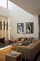 Simple curtain panels shield the neutrally furnished double-height living room from the hot afternoon sun