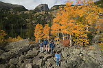 Family scrambles over boulders with golden colors of autumn in aspen stands and Hallett Peak above, all on a September morning above Bear Lake in Rocky Mountain NP, Colorado