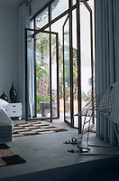 A series of pivoting glass doors opens from the simply furnished bedroom to the garden