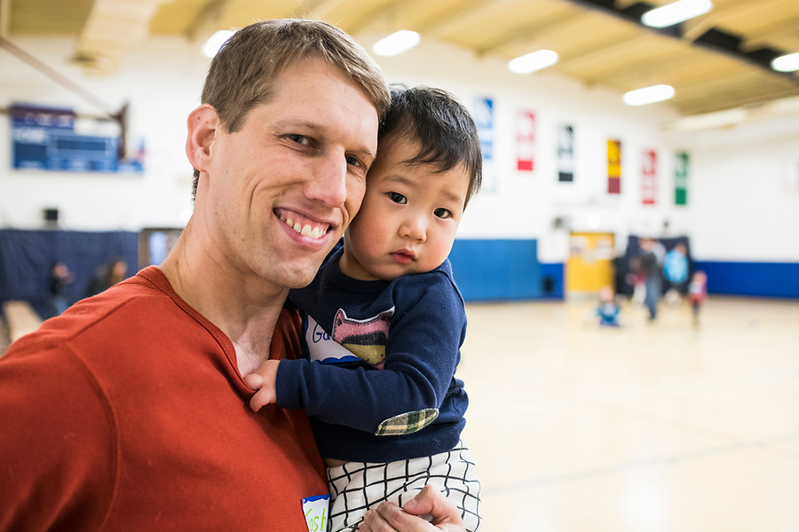 New member Josh Ciolkosz is pictured with his recently adopted son, Gabe, during a lunar new year event hosted by Families Through Korean Adoption (FTKA) in the gym and school cafeteria of St. Dennis Church in Madison, Wis., on Feb. 10, 2018. The event celebrated the passing of the lunar new year, and is one of several events for FTKA-member families and children to gather and enjoy cultural fun, food and play. (Photo by Jeff Miller - www.jeffmillerphotography.com)