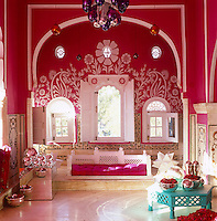 A carved turquoise table sits in sharp contrast to the shocking pink and white of the living room