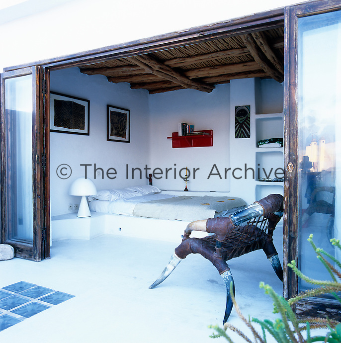 This bedroom opens directly onto the terrace and is furnished with a built-in platform bed and an unusual chair made of cattle horn