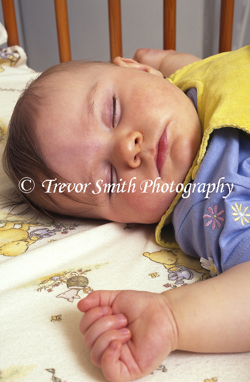 Baby sleeping on his back in a cot