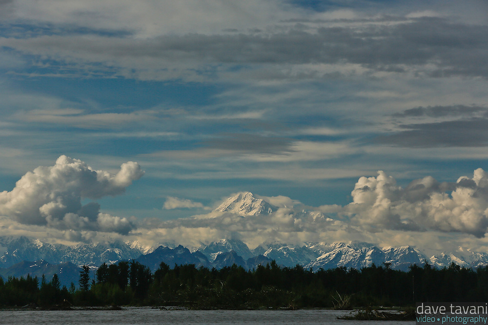 Clouds pass in front of Mt. McKinley (Denali), the highest peak in North America, but not enough to obscure the north and south summits. This view of Mt. McKinley and the Alaska Range is from Talkeetna, AK at the confluence of the Susitna, Chulitna, and Talkeetna Rivers.