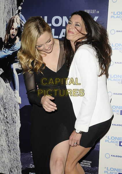MELISSA GEORGE & KATE MAGOWAN.UK premiere of 'A Lonely Place To Die' at Empire Leicester Square, London, England. .September 7th, 2011.half length black dress  white blazer sheer sleeves slit split side smiling laughing funny .CAP/CAN.©Can Nguyen/Capital Pictures.