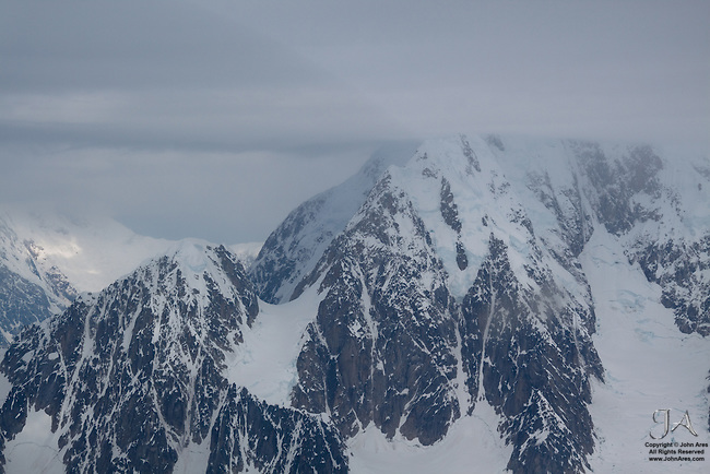 Aerial view of the south face of Mount McKinley / Denali with summit shrouded in clouds.