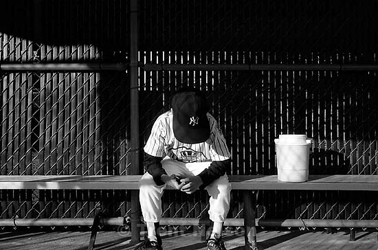 Player in dugout with head down at Yankees game<br />