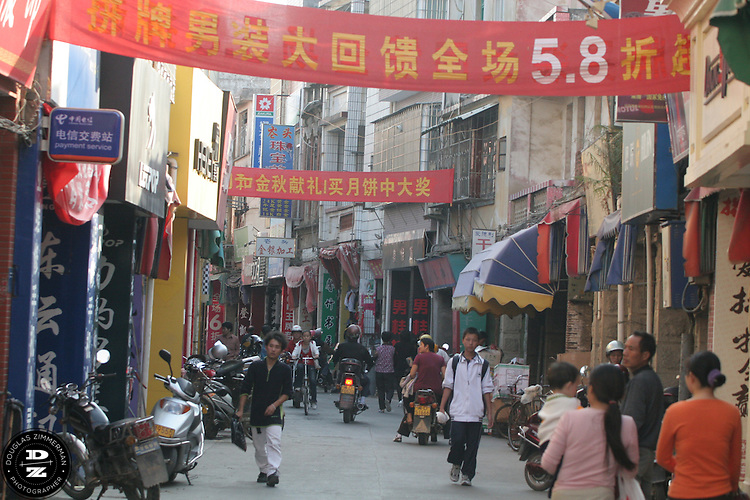 Pedestrians walk down the main shopping street of Maxiang Jie in Maxiang, China. The village,  north of the city of Xiamen, has grown from a small village into a large suburb over the past several years as construction and industry have arrived in the area.  Photograph by Douglas ZImmerman