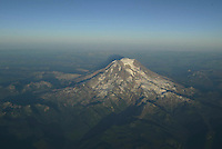 Mount Rainier seen as sun sets from an airplane above the mountain range.