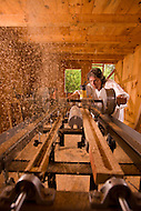 North Carolina gun and guitar maker, Bobby Denton, cuts wood on a large table saw in his workshop.