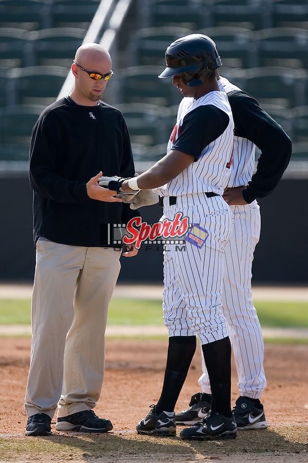 Trainer Chris McKenna inspects the left hand of Sergio Morales (15) after he was hit by a pitch versus the Asheville Tourists at Fieldcrest Cannon Stadium in Kannapolis, NC, Wednesday April 9, 2008.