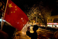 A man looks at Chinese and Olympic flags for sale from a street vendor on a street corner in Nanjing, China, the night before the Olympic Torch Relay arrives in Nanjing.