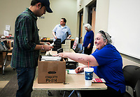 NWA Democrat-Gazette/CHARLIE KAIJO Volunteer Kay Jones (from right) reacts as she sells books to Bipin Jadhav of Bentonville during a book sale, Thursday, October 4, 2018 at the Bentonville Public Library in Bentonville.<br />