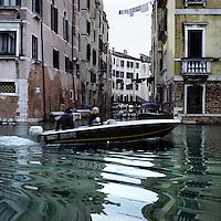 Venezia: una barca percorre un canale..Venice: a boat along a canal