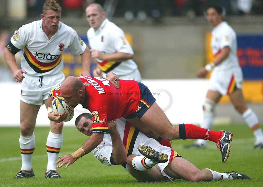 Photo Aidan Ellis..Bradford Bulls v London Broncos (Tetley Bitter Superleague) 01/06/2003..London's Steele Retchless is tackled by Bradford's Scott Naylor......