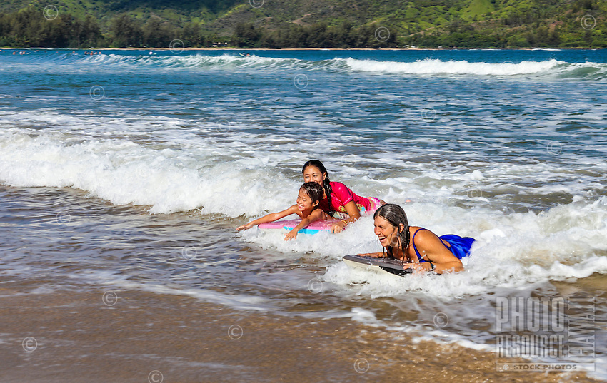 A mother and her children ride their boogie boards in to shore at Hanalei Beach, Kaua'i.