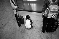 Landscape view of a child sitting on a subway platform in front of retail marketing signage at a B?ij?ng dìti?zhàn in D?ngchéng Q? in Beijing.  © LAN