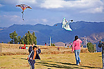 One young boy runs toward camera holding kite string with kite flying in the sky as teen girl flies her kite next to him in Saqsayhuaman National Park in Peru