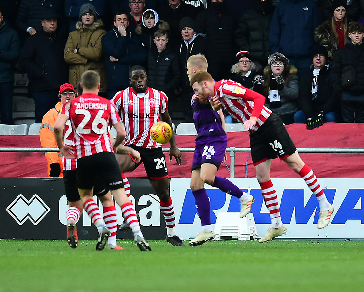 Lincoln City's John Akinde, left, and Cian Bolger combine to clear under pressure from Grimsby Town's Harry Davis<br /> <br /> Photographer Andrew Vaughan/CameraSport<br /> <br /> The EFL Sky Bet League Two - Lincoln City v Grimsby Town - Saturday 19 January 2019 - Sincil Bank - Lincoln<br /> <br /> World Copyright &copy; 2019 CameraSport. All rights reserved. 43 Linden Ave. Countesthorpe. Leicester. England. LE8 5PG - Tel: +44 (0) 116 277 4147 - admin@camerasport.com - www.camerasport.com