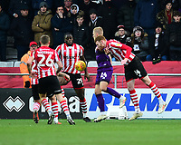 Lincoln City's John Akinde, left, and Cian Bolger combine to clear under pressure from Grimsby Town's Harry Davis<br /> <br /> Photographer Andrew Vaughan/CameraSport<br /> <br /> The EFL Sky Bet League Two - Lincoln City v Grimsby Town - Saturday 19 January 2019 - Sincil Bank - Lincoln<br /> <br /> World Copyright © 2019 CameraSport. All rights reserved. 43 Linden Ave. Countesthorpe. Leicester. England. LE8 5PG - Tel: +44 (0) 116 277 4147 - admin@camerasport.com - www.camerasport.com