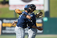 Asheville Tourists relief pitcher Justin Lawrence (27) gets a hug from catcher Campbell Wear (35) after closing out the win over the Kannapolis Intimidators at Kannapolis Intimidators Stadium on May 7, 2017 in Kannapolis, North Carolina.  The Tourists defeated the Intimidators 4-1.  (Brian Westerholt/Four Seam Images)