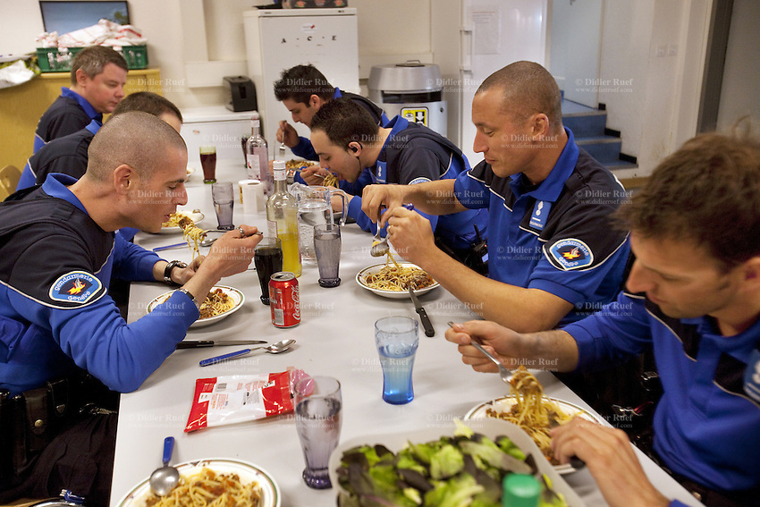 Switzerland. Geneva. Paquis police station. A group of police officers eat supper during a night shift. A plate of Spaghetti Bolognese with soft drinks and water. Bolognese sauce is a meat-based (beef or pork) sauce to dress various types of pasta. A police station or station house is a building which serves police officers and contains offices, temporary holding cells and interview/interrogation rooms. 18.05.12 © 2012 Didier Ruef