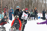 Grayson Bruton and team run past spectators on the bike/ski trail near University Lake with an Iditarider in the basket and a handler during the Anchorage, Alaska ceremonial start on Saturday, March 7 during the 2020 Iditarod race. Photo © 2020 by Ed Bennett/Bennett Images LLC