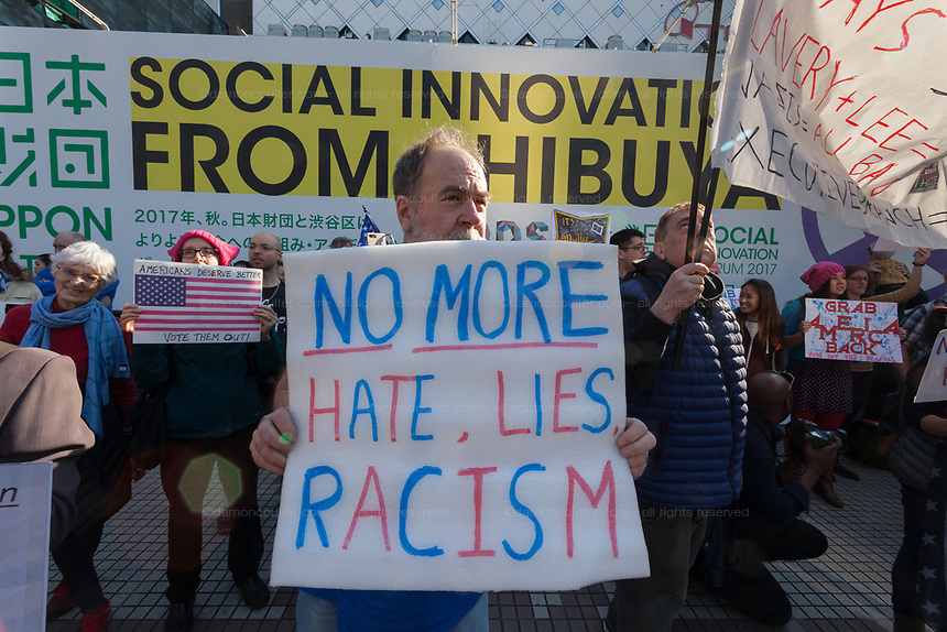 "Bob Murry from Texas holds a sign saying, ""No more Hate, lies, Racism"" at the Vote Out the Scandal rally at Hachiko Square, Shibuya, Tokyo, Japan. Sunday November 5th 2017. Timed to coincide with President Trumps visit to Japan, About 120 Americans living in Japan and some local Japanese  protested together from 2pm to 4pm to encourage US citizens to register to vote in future elections and call on the US government to honour it responsibilities to the American people,."