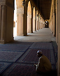 Cairo, Egypt -- Bright light shines through lovely arched openings into the arcades surrounding the central plaza and fountain at the historic ibn Tulun mosque.   © Rick Collier / RickCollier.com.