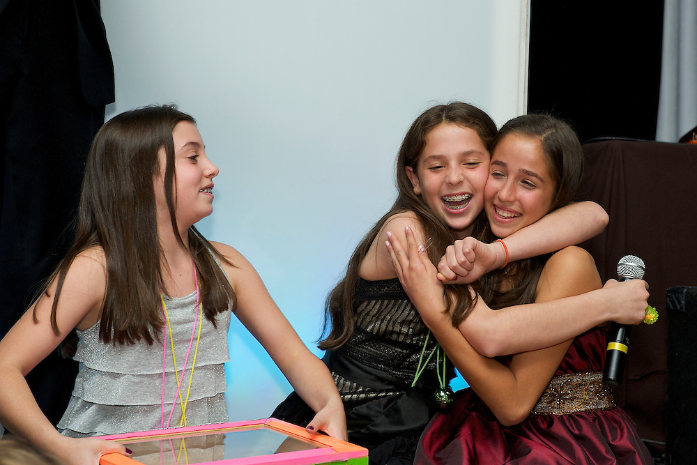 The Bat Mitzvah girl being hugged by a friend.