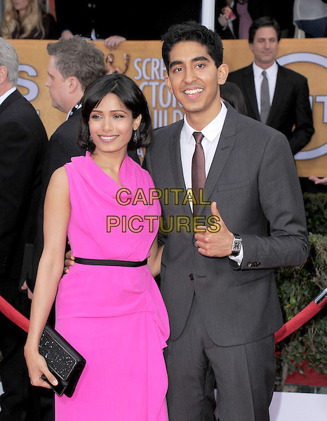 Freida Pinto (wearing Roland Mouret) & Dev Patel .Arrivals at the 19th Annual Screen Actors Guild Awards at the Shrine Auditorium in Los Angeles, California, USA..27th January 2013.SAG SAGs half length pink dress grey hand thumb up gray suit couple black clutch bag draped.CAP/DVS.©DVS/Capital Pictures.