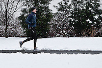 Snow falls as a man runs in Jersey City during the season's first snow storm on December 10, 2013 in New York City Photo by Kena Betancur / VIEWpress.