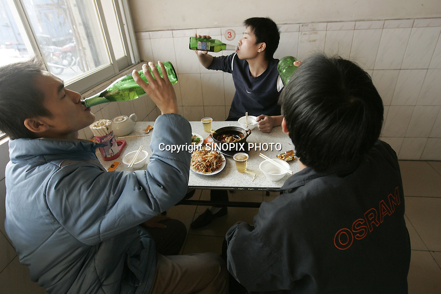 Workers, (L) Light blue jacket, Qian Wen Jun (M) at rear facing the camera Luo Zhi Yong (R) face concealed with Osram jacket Chen Cey at a canteen outside the  Osram factory in Foshan city, Guangdong Province, China, 16th January 2008. Osram China Lighting Ltd make energy saving light bulbs that are sold in the UK.
