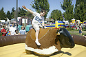 Boy riding mechanical bull at Whaling Days festival, Silverdale, WA Kitsap County community event. Stock photography by Olympic Photo Group