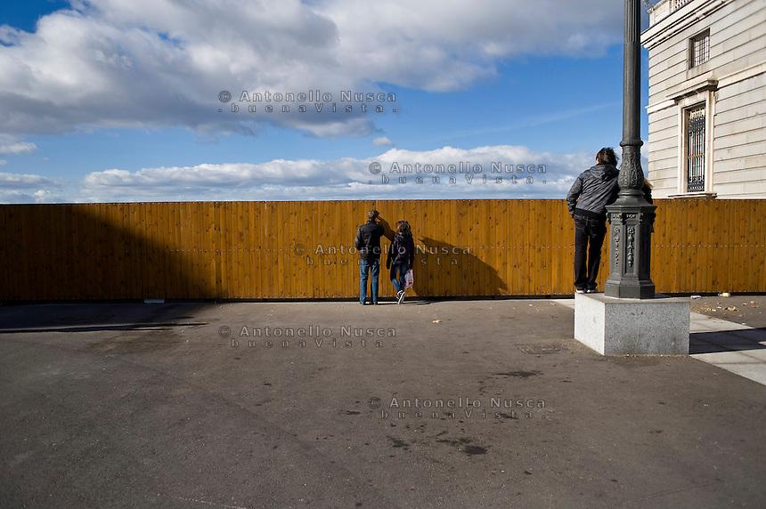 Alcuni turisti cercano di guardare il panorama di Madrid dalla Plaza d'Oriente attraverso la fessura di una palizzata di legno