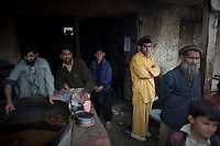 Villagers watch as marines patrol in Nishigham village Nuristan. The day's mission was to re-supply an OP (Observation Post) that had been attacked the day before killing one ANA (Afghan National Army) soldier. The marines are acting as an ETT (Embedded Training Team) to mentor the ANA with the ultimate aim of leaving the country's security for the local Army to deal with.