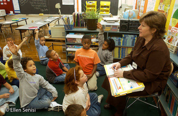 MR / Schenectady, NY.Yates Arts in Education Magnet School, Grade 2.Arts-Themed Urban Elementary School.Students raise hands as teacher does reading lesson from reading series textbook with class..MR: g2c.© Ellen B. Senisi