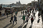 Venice Italy 2009. Tourists walk along the Pizzetta at Saint Marks Square Piazza San Marco. The church of Santa Maria della Salute.<br /> <br /> Venice is sinking under the weight of 20 million visitors a year. Only 30% of Venice's visitors stay overnight the rest stay out of town or on their cruise ships. There is a plan is to limit visitors to the city who have pre-booked hotel accommodation.